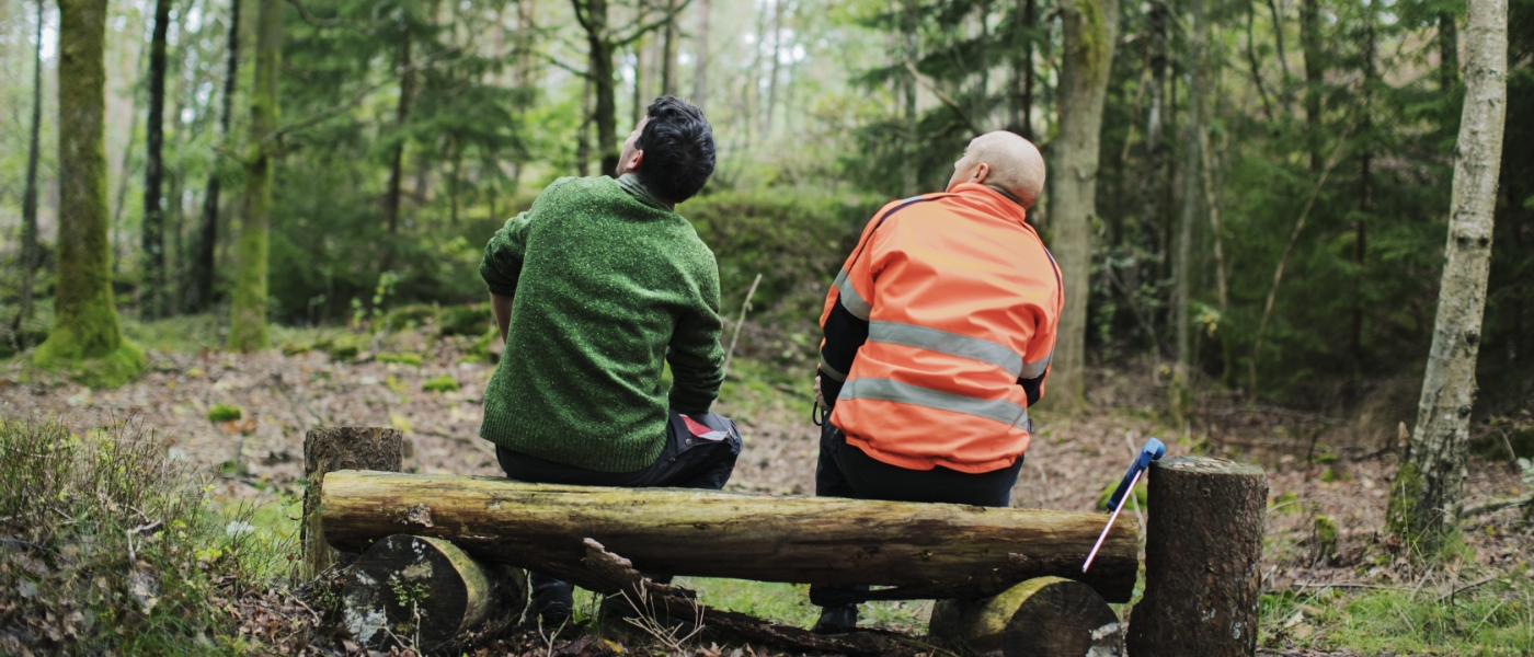 Två män sittandes i skogen